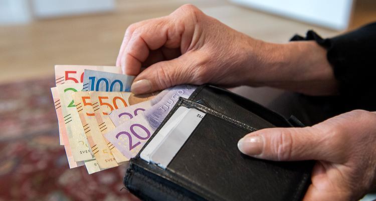 Bilden visar en person som tar ut sedlar ur en plånbok. Vi ser bara plånboken och händerna.
