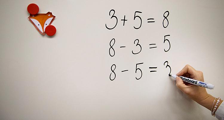 Någon skriver siffror på en tavla