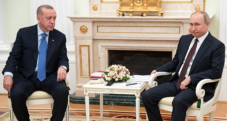Erdogan sitter bredvid Putin. Mellan dem ett litet bord. Bakom dem en stor tom eldstad i vitt och guld.