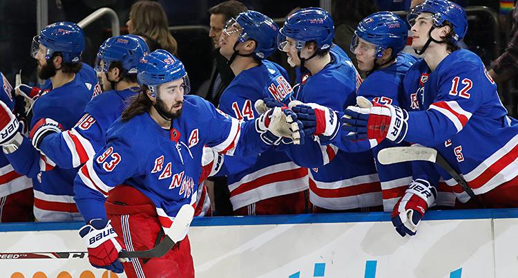 Bilden är från en match i ishockey. En spelare åker längs sargen och boxar sin handske mot handskarna på de andra i sitt lag. Det är ett sätt att gratulera.