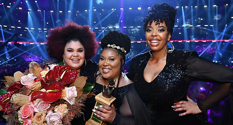 De tre kvinnorna ser glada ut och håller i blommor och i ett pris