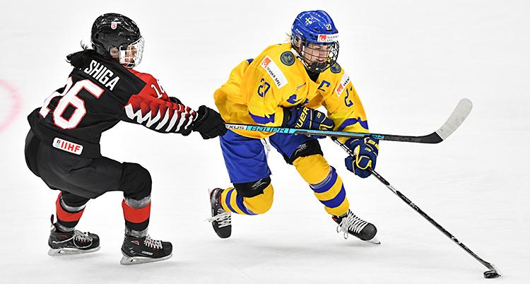 En bild från en match. En svensk spelare dribblar med pucken.