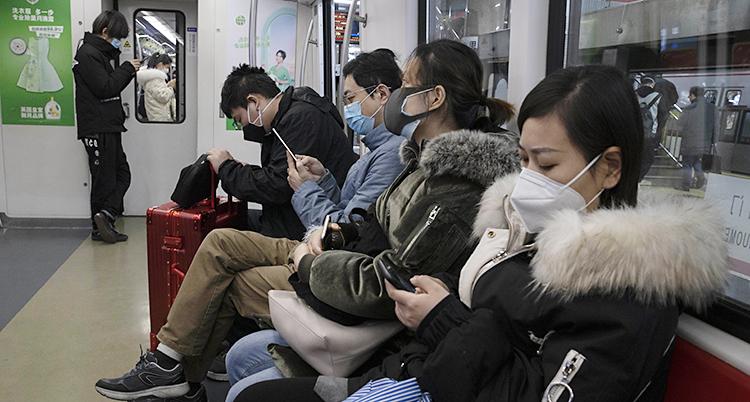 Bilden visar människor som sitter i en vagn i tunnelbanan. De har skydd över näsan och munnen.