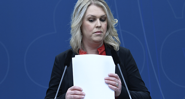 Ministern ser allvarlig ut och håller en bunt papper i handen.