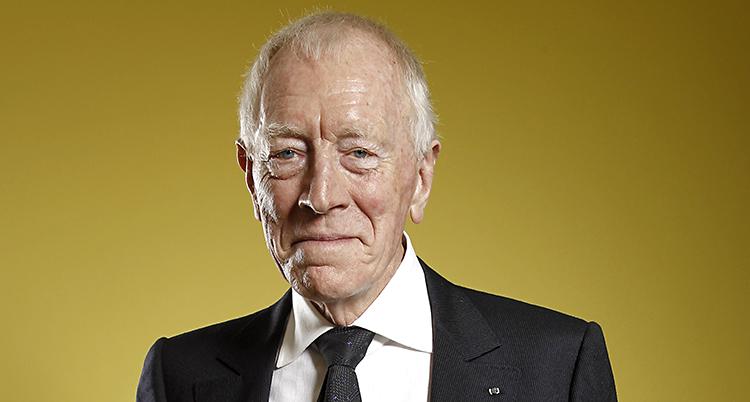 En äldre man med kostym står framför en gul vägg