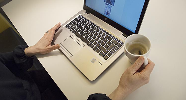 Två armar och händer sticker fram vid en dator. Bredvid står en kopp kaffe