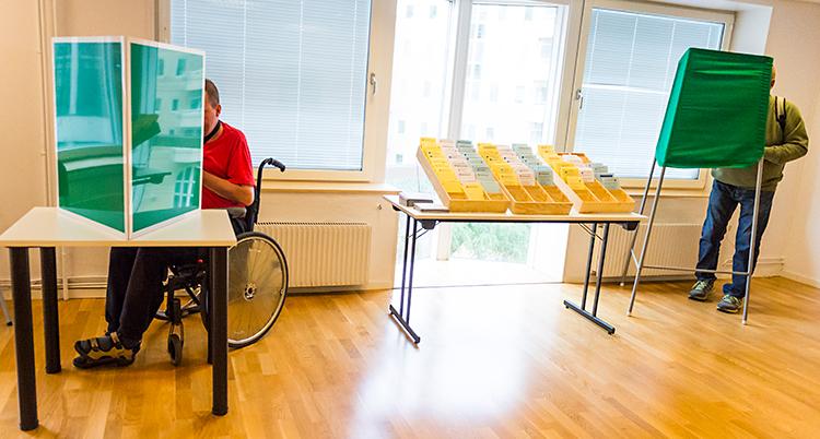 Bilden visar en lokal för att rösta. En person i en rullstol är bakom en grön skärm. En annan person står bakom en annan grön skärm.
