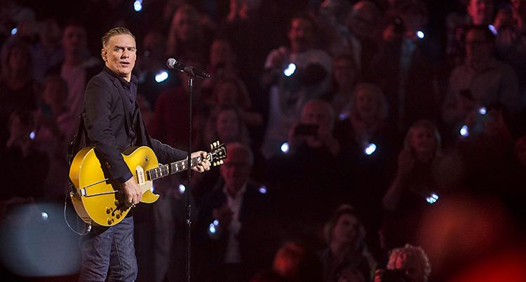 Bryan Adams står på en scen med sin gitarr. I bakgrunden syns publiken. Många håller upp sina mobiltelefoner som lyser.