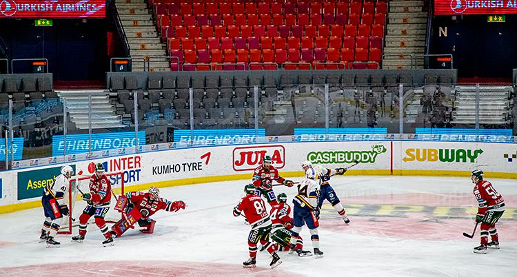 Två lag som spelar en match i ishockey. Det är tomt på läktarna. Ingen publik är där.