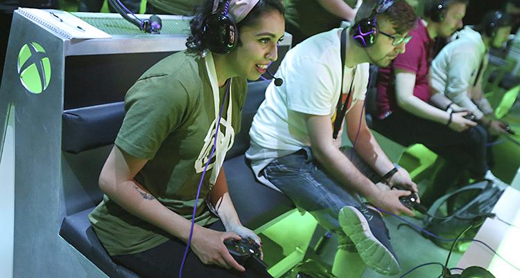 Flera personer sitter och spelar datorspel. De har kontroller i händerna