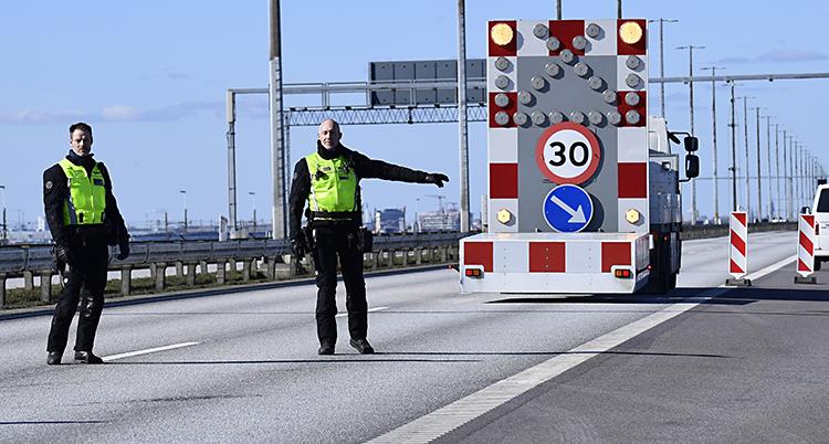 Två poliser i gula västar. Pekar åt en bil att svänga åt sidan