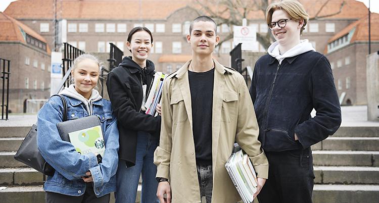 Fyra ungdomar ser glada ut och bär böcker och papper i famnen