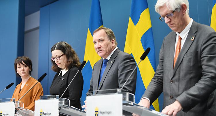 Två kvinnor och två män står framför svenska flaggor och pratar i mikrofon