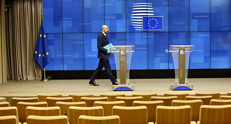 En man går framför en blå vägg med EUs flagga