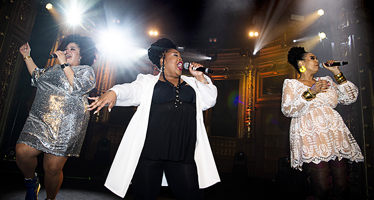 Tre kvinnor i glittriga kläder sjunger i mikrofon