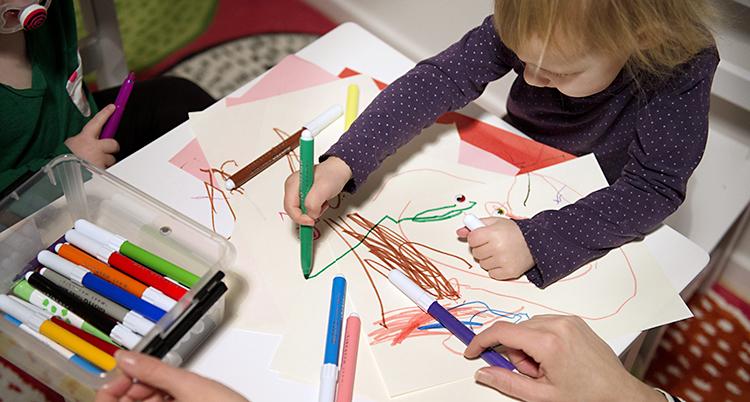 Ett barn sittre och ritar vid ett bord
