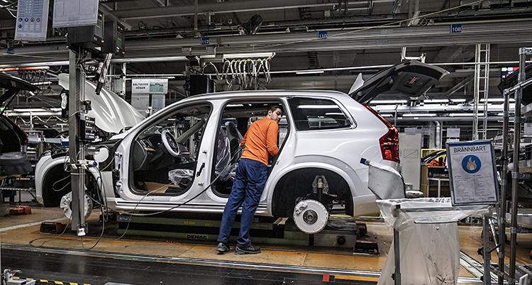 En person jobbar med en bil på en fabrik