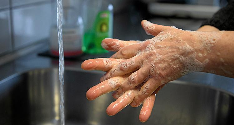 Bilden visar två händer. De är löddriga med tvål. Vi ser också en kran där vattnet rinner.