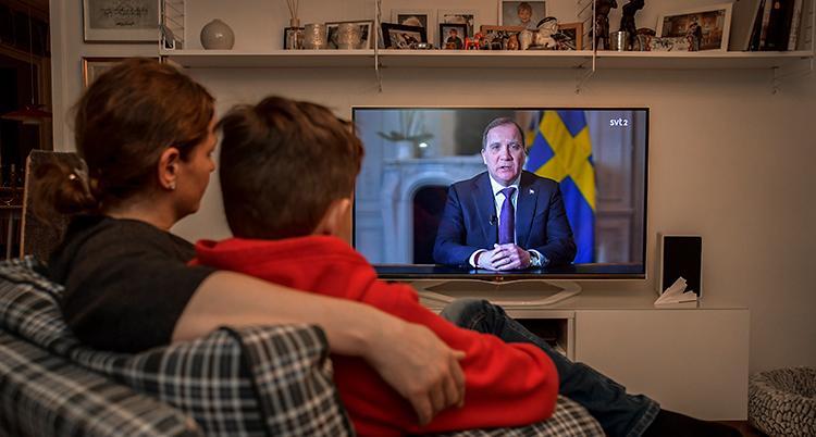 Ett vardagsrum i ett hem. En kvinna och en pojke sitter i en soffa. De tittar på tv.