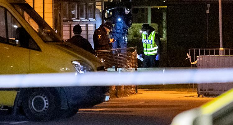 Bilden är tagen utomhus. Det är mörkt. Tre poliser håller på och jobbar.