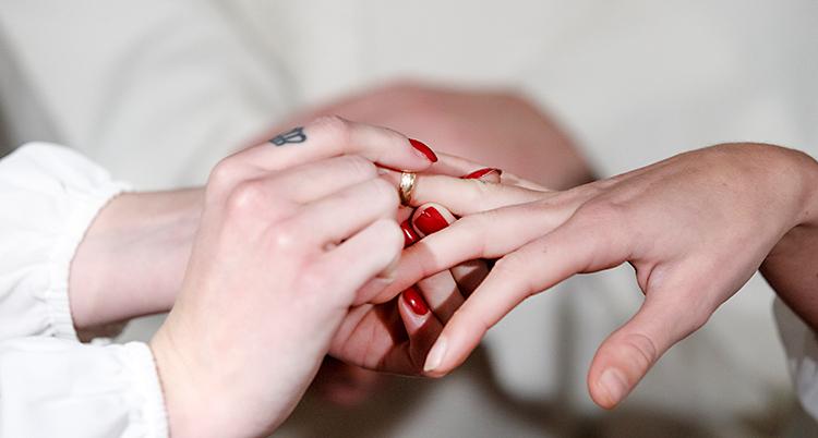Bilden visar händerna från två personer. Den ena personen sätter en ring på fingret på den andra.
