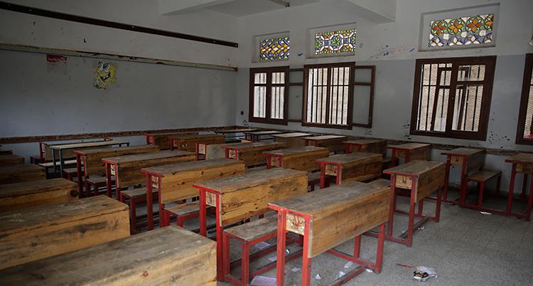 Ett klassrum med bänkar av trä.