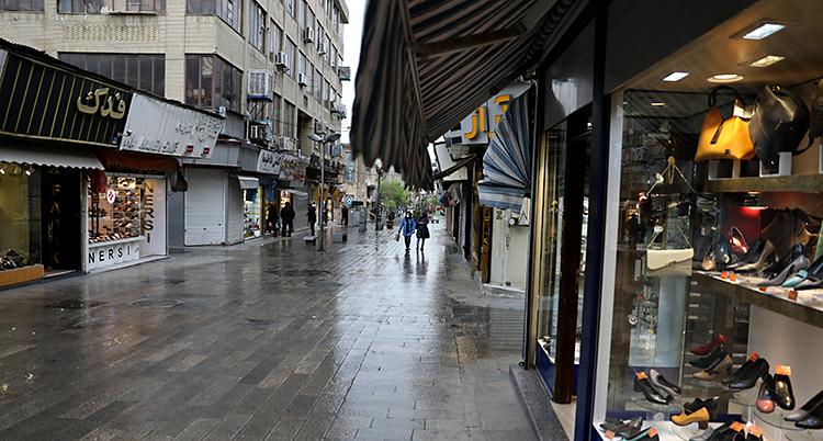 Bilden visar en gata i staden Teheran. Det är grått väder och regnar. Det syns en affär som säljer skor. Långt bort i bilden syns några få människor.