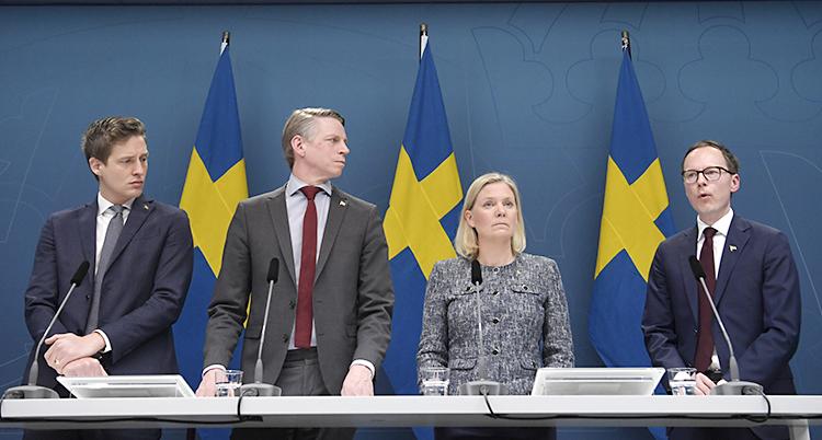 Tre män och en kvinna på rad framför svenska flaggor