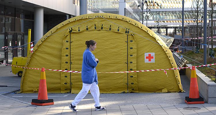 En kvinna i sjukvårdskläder går utanför ett stort gult tält