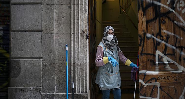 Kvinnan har sjal över håret och städkläder. Hon står i en port med städgrejer