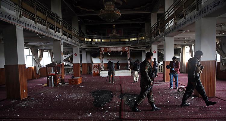 Bilden visar insidan av ett tempel. På golvet ligger röda mattor. Det är högt i tak. I taket hänger en ljuskrona.
