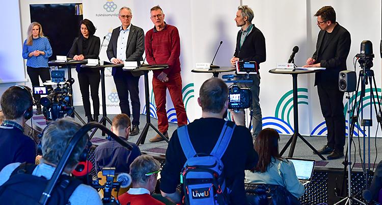 Flera personer står på en scen och pratar i mikrofoner. Framför scenen finns det journalister.