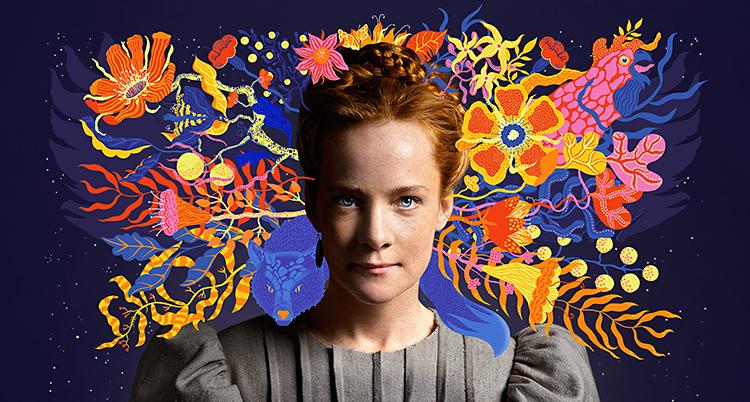 Bilden visar en ung kvinna med rött hår. Hon tittar in i kameran. Bakom henne syns en målning med massa blommor i starka färger.