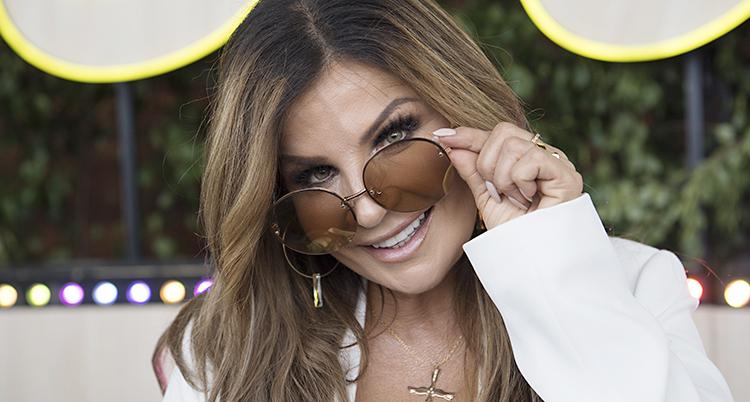 Carola ser glad ut och kikar fram bakom stora solglasögon