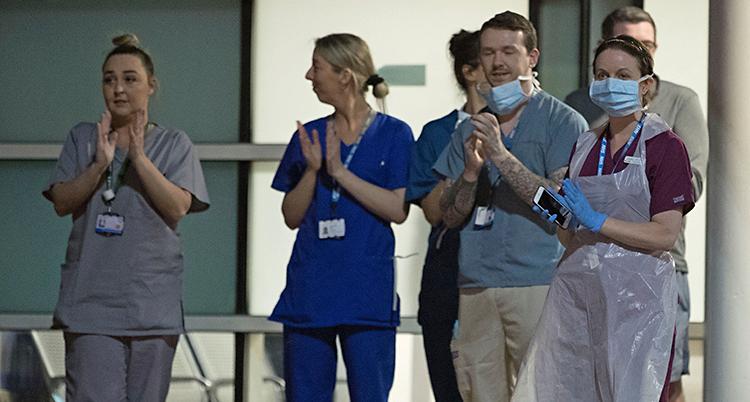Flera personer står utanför ett sjukhus. De jobbar på sjukhuset. De har på sig sina jobbkläder.