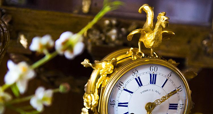 En gammaldags klocka i guld med en tupp på