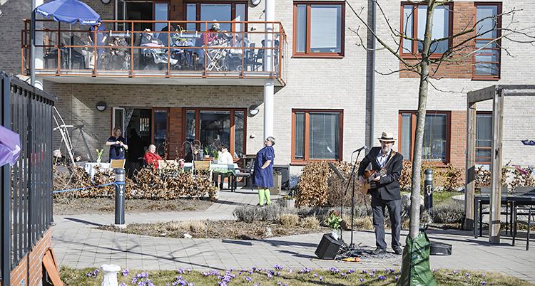 En man med gitarr och mikrofon spelar. De gamla sitter ovanför på en balkong. Solen skiner.