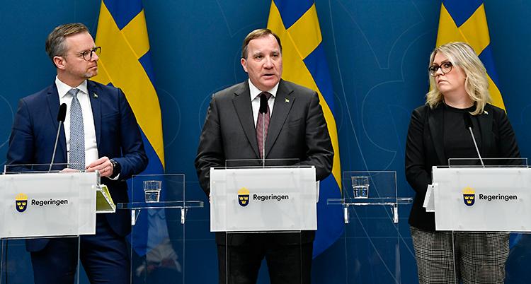 Tre politiker står på en scen. De talar i mikrofoner. I bakgrunden syns svenska flaggor.