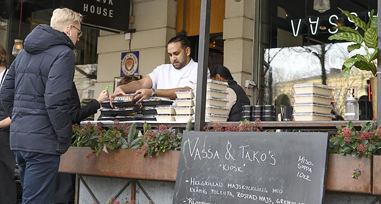 En servitör staplar upp lådor med mat utanför en restaurang
