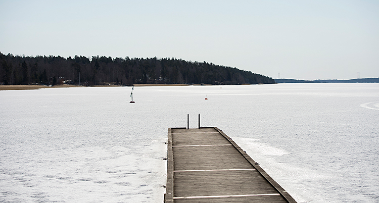 Bilden visar en sjö på vintern. Det är is och snö på sjön. En brygga av trä går ut i sjön.