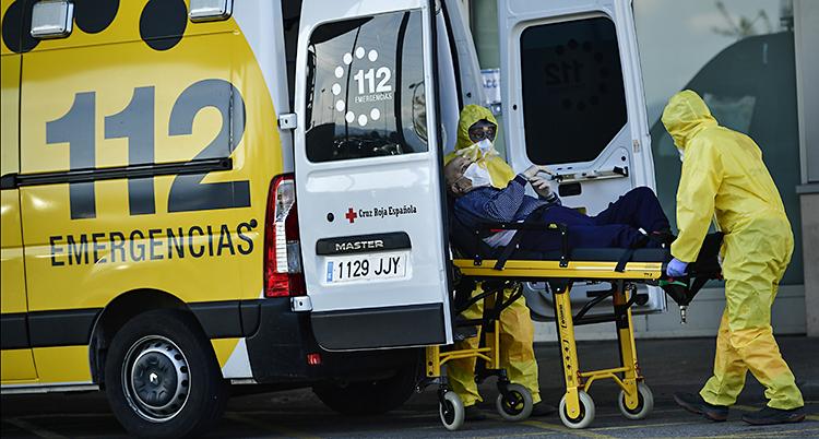 Sjukvårdarna har skyddsutrustning. De rullar ut en bår med en gammal människa
