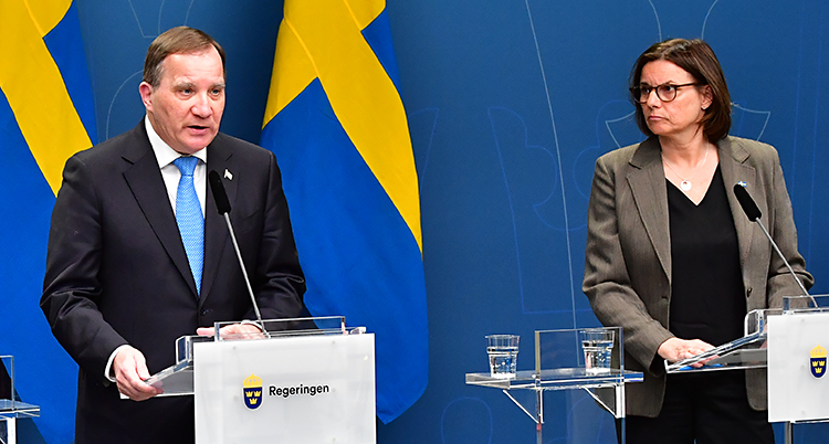 De står på en scen och pratar i mikrofoner. Bakom dem finns svenska flaggor. I rummet finns många journalister.