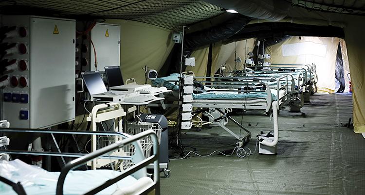Flera sängar står på rad. De står inne i ett tält.