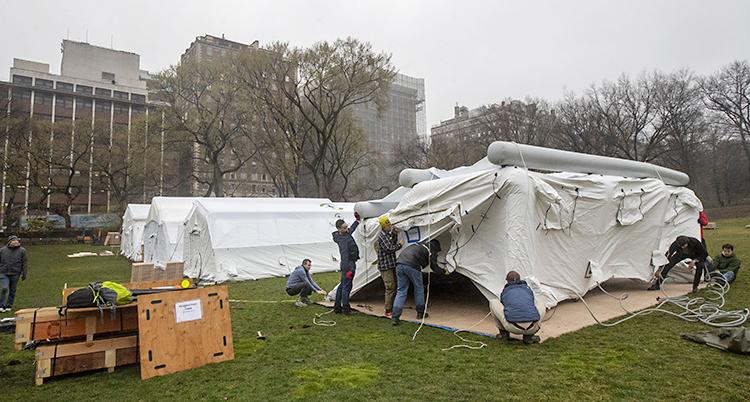 Människor reser ett vitt tält. Bredvid tältet syns flera andra tält.