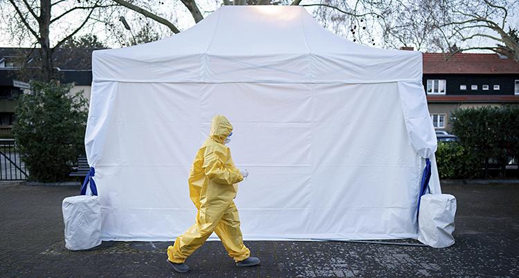 Ett vitt tält syns. Framför det går en läkare i gula skyddskläder.