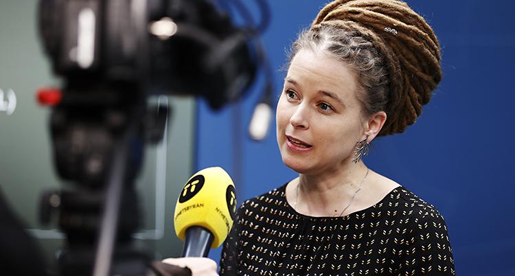 Kvinnan talar med en reporter som har en gul mikrofon i handen.