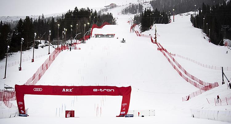 Bilden visar en tom slalombacke i Åre. Det är snö på marken och målet är rött. De är röda stängsel längs backen. Det syns också träd bredvid backen.