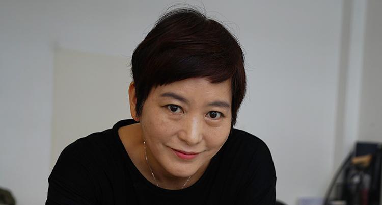 En sydkoreansk kvinna tittar in i kameran. Hon ler. Hon har kort, mörkt hår.