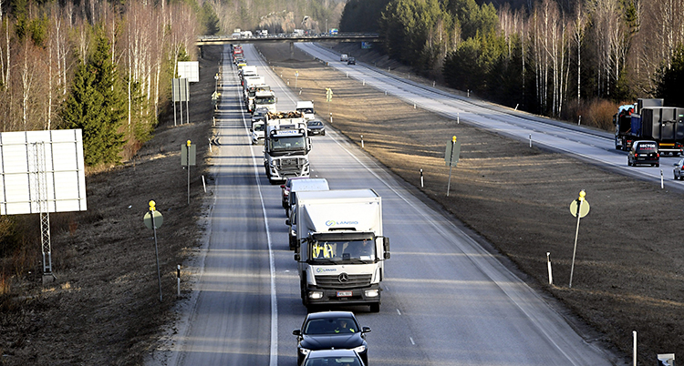 En motorväg med många bilar och lastbilar efter varandra.