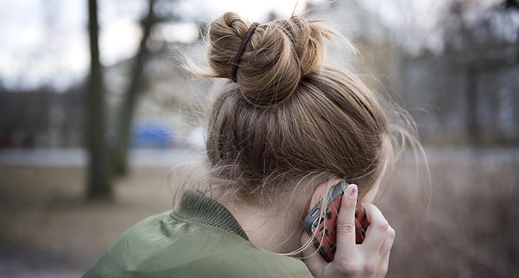 En flicka sitter med sin mobiltelefon vid örat.